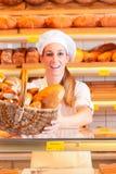 卖面包的女性面包师在她的面包店 免版税库存照片