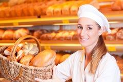 卖面包的女性面包师在她的面包店 图库摄影