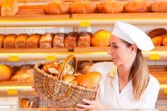 卖面包的女性面包师在她的面包店 免版税库存图片
