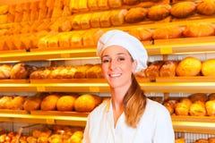 卖面包的女性面包师在面包店 免版税库存图片