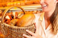 卖面包的女性面包师由篮子在面包店 库存照片