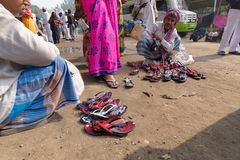 卖鞋子的卖主对莎丽服穿的印地安妇女,加尔各答,印度 免版税库存照片