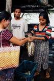 卖鱼的地方少妇在与她的丈夫的村庄市场上 免版税库存照片