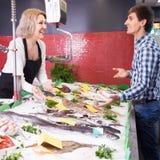 卖鱼的微笑的妇女对男性顾客在商店 免版税库存照片