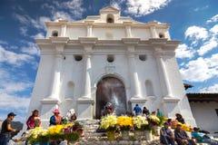 卖黄色花罗马天主教堂奇奇卡斯特南戈集市日危地马拉的本地人 库存图片