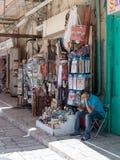 卖主在Muristan街的纪念品店附近坐在老城耶路撒冷,以色列 库存照片