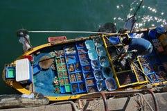 卖从她的小船的妇女鲜鱼 图库摄影