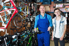 卖主帮助的男孩在体育商店选择自行车 免版税库存照片