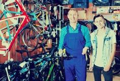卖主帮助的男孩在体育商店选择自行车 库存照片