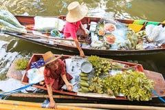 卖水果和蔬菜在一个传统浮动市场上的老妇人 图库摄影