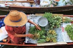 卖水果和蔬菜在一个传统浮动市场上的老妇人 免版税库存照片