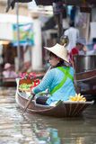 卖fruirs的妇女在浮动市场上 免版税库存图片