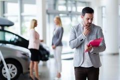 卖vehichles的售车行的英俊的推销员 库存图片