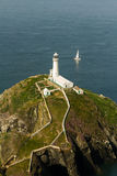 南堆灯塔, Anglesey,与白色航行游艇 免版税库存图片