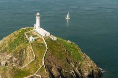 南堆灯塔, Anglesey,与白色航行游艇 免版税库存照片