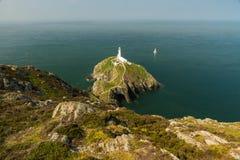 南堆灯塔, Anglesey,与白色航行游艇 免版税图库摄影