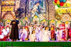 南定市,越南- 2014年12月24日-唱在圣诞前夕的基督徒信徒圣诞颂歌 图库摄影