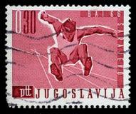 南斯拉夫打印的邮票在萨拉热窝显示跳远,巴尔干比赛 库存图片