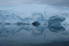 南极洲冰川在镜子蓝色海湾反射在阴天 库存照片