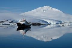 南极洲小船在白雪下的蓝色海湾加盖山的镜子起波纹 库存照片