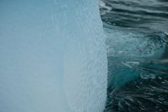 南极洲独特的发光的蓝色冰山艺术纹理在起波纹的水中 图库摄影