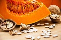 南瓜、坚果和种子在桌上 免版税库存照片