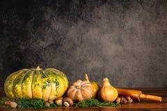 南瓜、胡桃和蘑菇与滚针在一张桌上在葡萄酒背景与拷贝空间 免版税库存图片