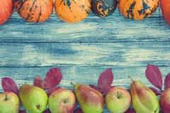 南瓜、苹果、梨和秋叶在木背景 库存图片