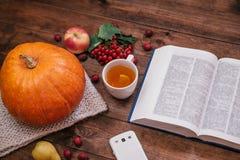 南瓜、苹果和书,在木桌上的电话的顶视图 免版税图库摄影