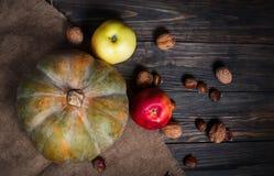 南瓜、苹果和坚果在木背景 库存图片
