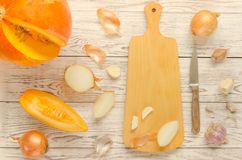 南瓜、葱、大蒜和切板有刀子的 库存图片