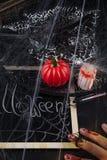 南瓜、蜡烛和一块长的玻璃与一个红色鸡尾酒 免版税库存照片