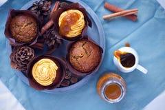 南瓜与buttercream和南瓜sirup的香料杯形蛋糕在具体灰色圆的盘子的松饼旁边在蓝色餐巾 免版税库存图片