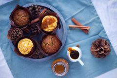 南瓜与buttercream和南瓜sirup的香料杯形蛋糕在具体灰色圆的盘子的松饼旁边在蓝色餐巾 库存图片