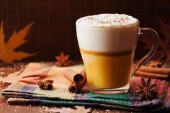 南瓜加了香料拿铁或咖啡在一块玻璃在一张土气桌上 秋天或冬天热的饮料 免版税库存图片