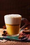 南瓜加了香料拿铁或咖啡在一块玻璃在一张木桌上 秋天或冬天热的饮料 图库摄影