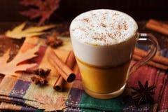 南瓜加了香料拿铁或咖啡在一块玻璃在葡萄酒桌上 秋天或冬天热的饮料 免版税库存照片