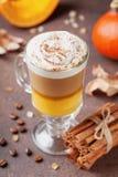 南瓜加了香料拿铁或咖啡在玻璃在棕色背景 秋天、秋天或者冬天热的饮料 库存照片