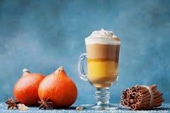 南瓜加了香料拿铁或咖啡在玻璃在深蓝桌上 秋天、秋天或者冬天热的饮料 图库摄影
