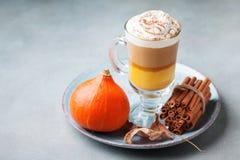 南瓜加了香料拿铁或咖啡在玻璃在石桌上 秋天、秋天或者冬天热的饮料 免版税库存图片