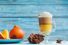 南瓜加了香料拿铁或咖啡在玻璃在绿松石土气桌上 秋天、秋天或者冬天热的饮料 免版税库存图片