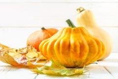 南瓜和小馅饼平底锅和槭树,橡木在一张白色木桌上的黄色叶子 秋天收获 库存照片