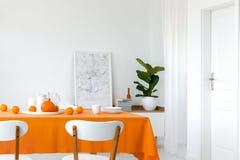 南瓜和桔子在餐桌,被构筑的地图上在堆书旁边在架子 免版税图库摄影