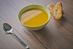 南瓜和红萝卜汤用薄脆饼干和荷兰芹在木背景与匙子和敬酒的面包切片 库存图片