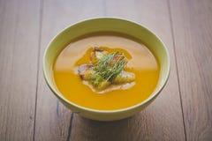 南瓜和红萝卜汤用薄脆饼干和荷兰芹在木背景与面包片 免版税库存照片