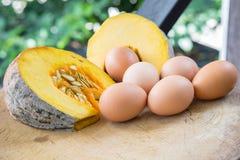 南瓜和许多鸡蛋在一个木切板 图库摄影