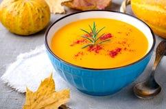 南瓜奶油色汤用迷迭香和辣椒粉在蓝色碗 万圣夜感恩秋天食物概念 库存照片