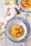 南瓜意大利煨饭和杯两块板材白葡萄酒 库存照片