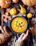 南瓜或红萝卜汤用油煎方型小面包片和草本在她的手上拿着一名妇女 秋天膳食食物 在视图之上 图库摄影