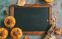 南瓜松饼和肉桂条有空的黑板的 免版税库存图片